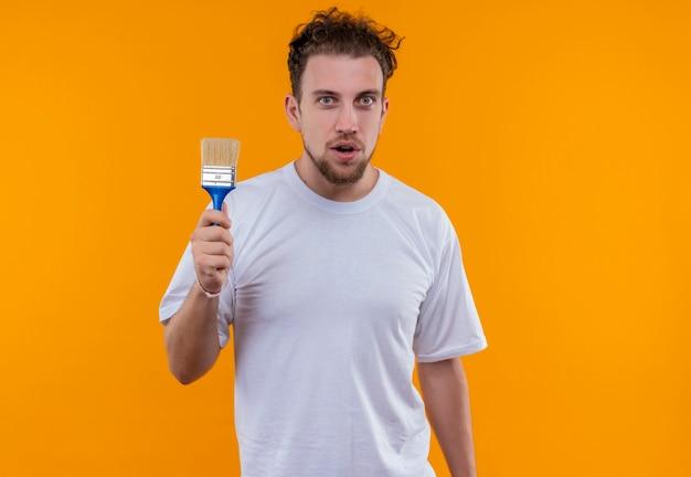 Junger mann, der weißen t-shirt hält pinsel auf isolierter orange wand hält
