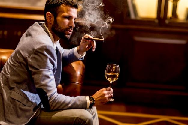 Junger mann, der weißen wein und rauchende zigarre schmeckt