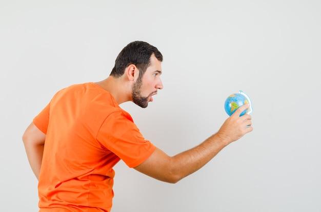 Junger mann, der weltkugel im orangefarbenen t-shirt betrachtet und konzentriert schaut.