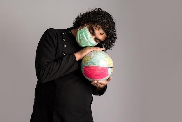 Junger mann, der weltkugel mit einer medizingesichtsmaske hält. welt-epidemie des coronavirus-konzepts.