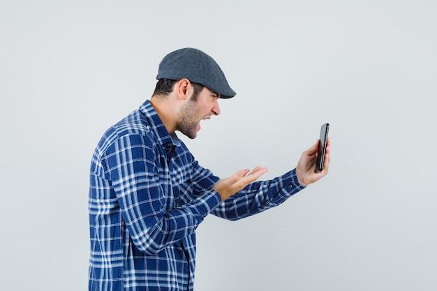 Junger mann, der wütend wird, während er etwas auf videoanruf im hemd, vorderansicht der kappe bespricht.