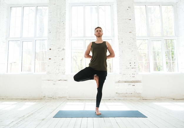 Junger mann, der yoga oder pilatesübung tut