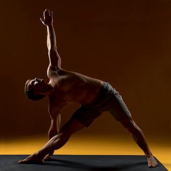 Junger mann, der yogaübung tut