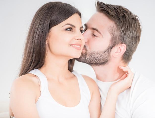 Junger mann, der zärtlich seine frau an der backe küsst.
