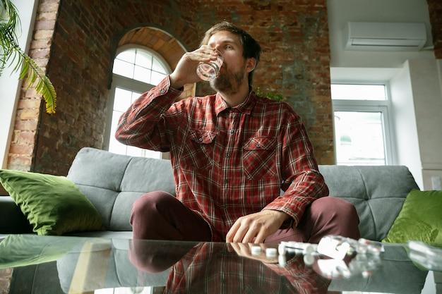 Junger mann, der zu hause bleibt, wasser trinkt und pillen nimmt