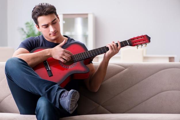 Junger mann, der zu hause das spielen der gitarre übt