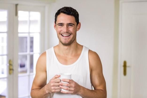 Junger mann, der zu hause kaffee in der küche lächelt und hält