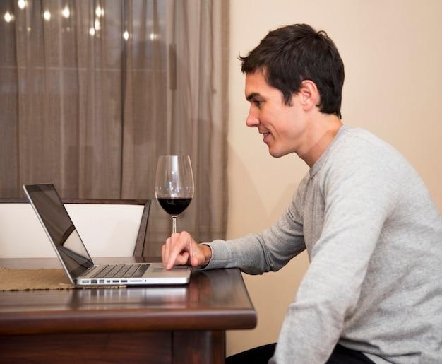 Junger mann, der zu hause laptop mit weinglas auf tabelle verwendet