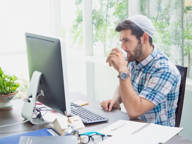 Junger mann, der zu hause mit kaffee arbeitet