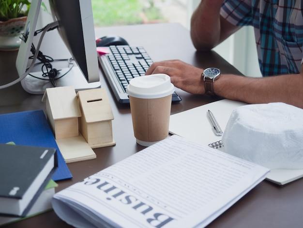 Junger mann, der zu hause mit kaffee und zeitung arbeitet