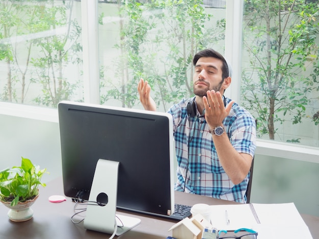 Junger mann, der zu hause mit kopfhörer arbeitet