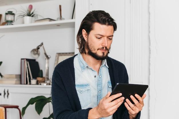 Junger mann, der zu hause sitzt, digitale tablette betrachtend