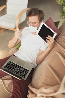 Junger mann, der zu hause während der online-kurse für desinfektor studiert