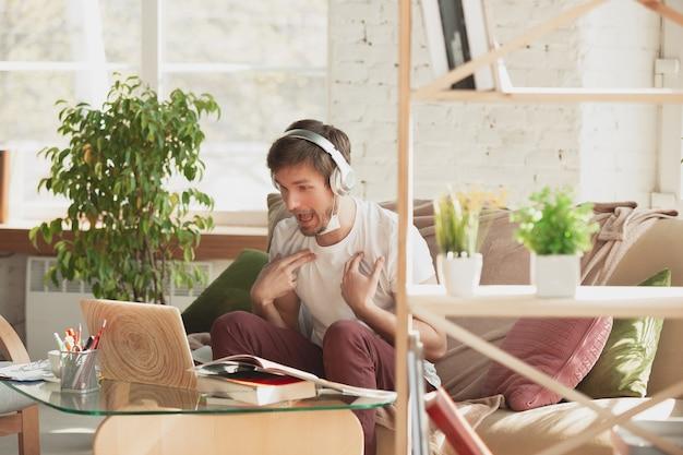 Junger mann, der zu hause während online-kursen für den übersetzer des marketing-architekten studiert