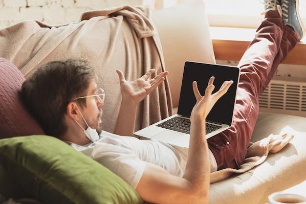 Junger mann, der zu hause während online-kursen für journalisten, kritiker, schriftsteller studiert.