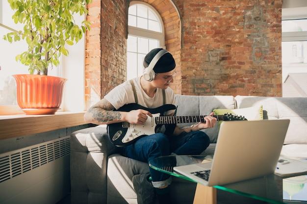 Junger mann, der zu hause während online-kursen oder kostenlosen informationen selbst studiert