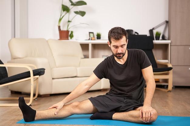 Junger mann, der zu hause yoga in seinem wohnzimmer praktiziert. er strampelt und fühlt sich entspannt