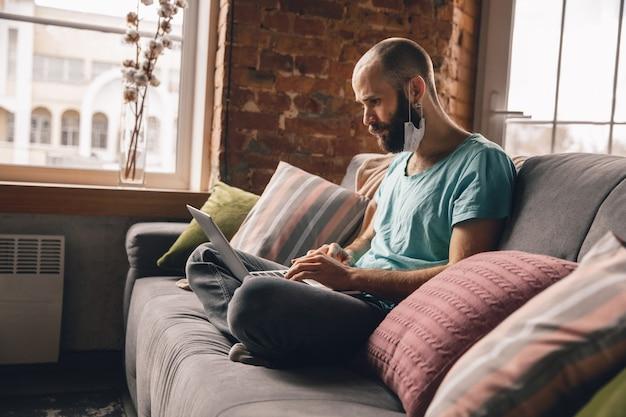 Junger mann, der zu hause yoga macht, während er unter quarantäne steht und freiberuflich online arbeitet