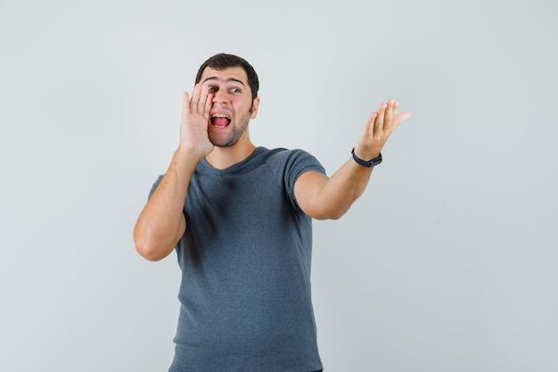 Junger mann, der zu jemandem in der grauen t-shirt-vorderansicht schreit.