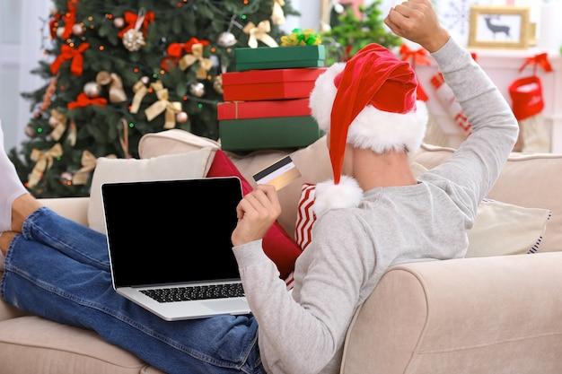 Junger mann, der zu weihnachten online mit kreditkarte zu hause einkauft
