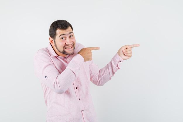 Junger mann, der zur seite im rosa hemd zeigt und optimistisch aussieht