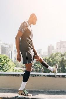 Junger mann des afrikanischen athleten, der sein bein auf dachspitze in der stadt ausdehnt