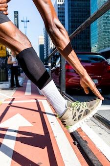Junger mann des athleten, der sein bein und hand auf bürgersteig in der stadt ausdehnt