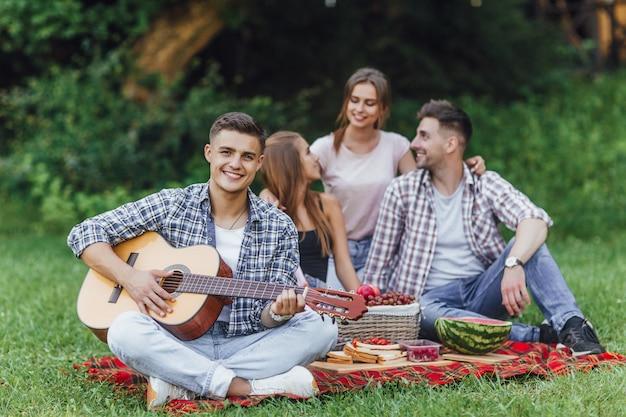 Junger mann des attraktiven brunette, der im gras sitzt und zur gitarre, picknick mit drei freunden spielt