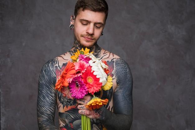 Junger mann des hemdlosen hippies mit tätowierung auf seinem körper, der gerbera hält, blüht in der hand