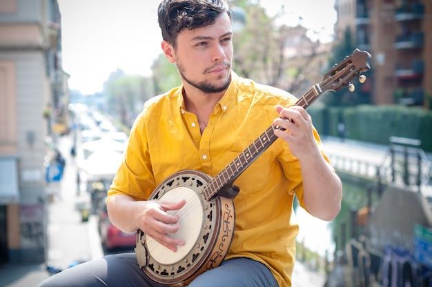 Junger mann des hippies, der banjo spielt