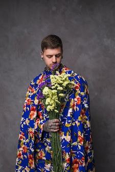 Junger mann des hippies mit tätowierung in seiner hand, die purpurrotes und gelbes limonium hält, blüht gegen graue wand