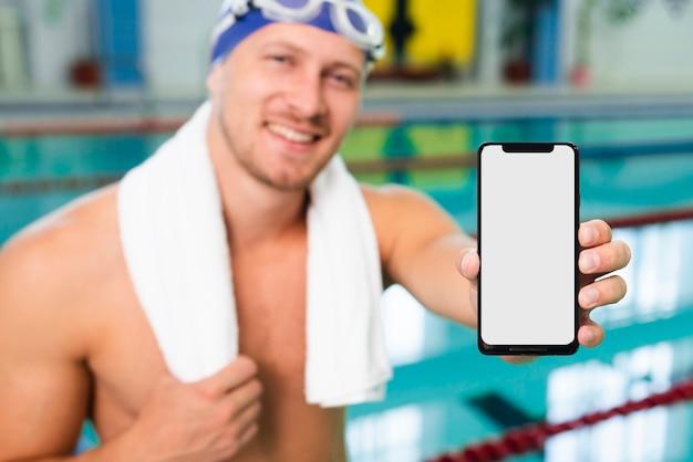 Junger mann des hohen winkels am pool, das mobile hält