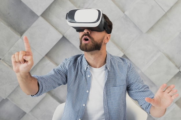 Junger mann des hohen winkels mit virtuellem kopfhörer