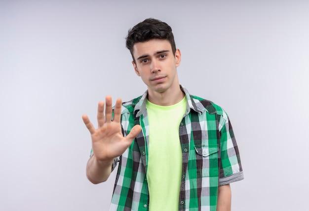 Junger mann des kaukasus, der grünes hemd trägt, das stoppgeste auf isolierter weißer wand zeigt