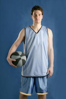 Junger mann des korbspielers über blau