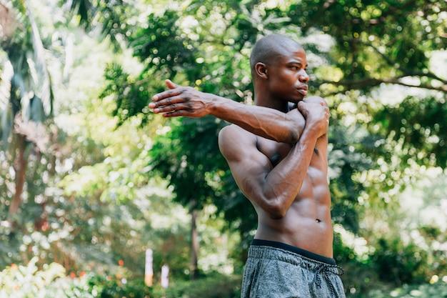 Junger mann des muskulösen athleten, der seine hand steht vor bäumen ausdehnt