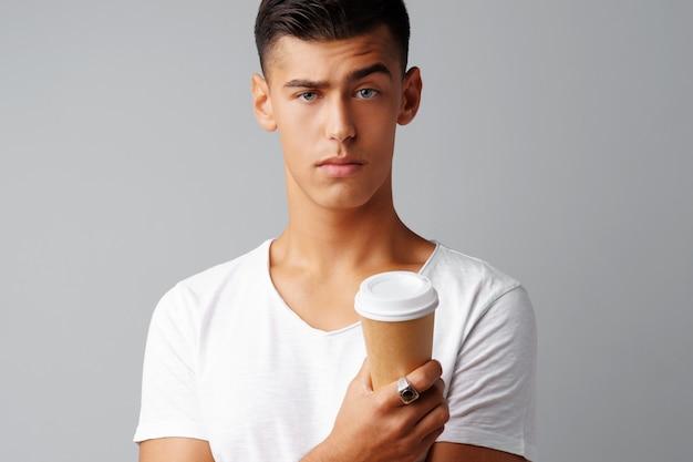 Junger mann des netten brunette, der einen tasse kaffee hält