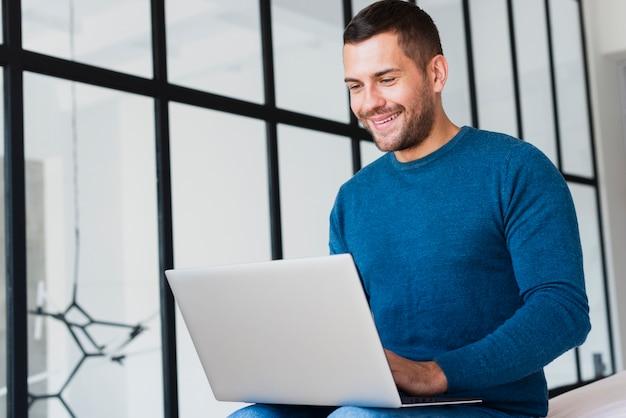 Junger mann des niedrigen winkels, der an laptop arbeitet