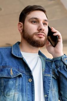Junger mann des porträts, der anruf macht. kaukasischer bärtiger geschäftsmann führt mobile gespräche und spricht drinnen telefoniert.