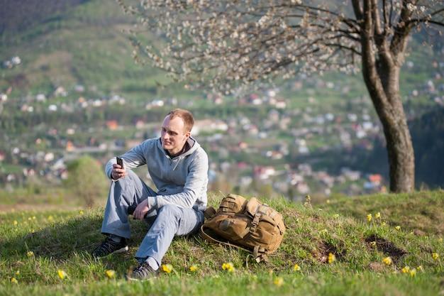 Junger mann des reisenden mit rucksack auf hügel