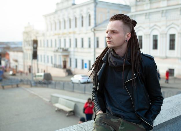 Junger mann des rockerrockstars, der am stadtstraßen-herbsttag geht