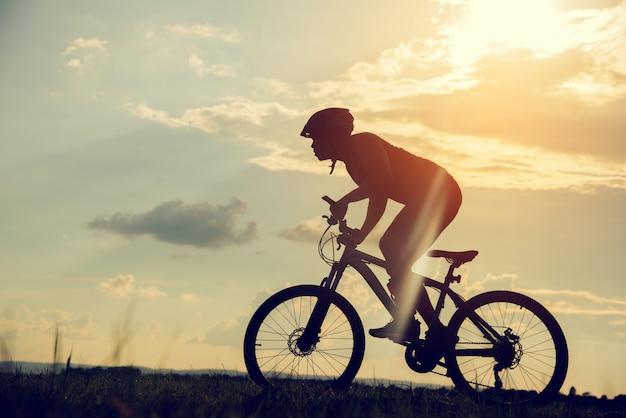 Junger mann des schattenbildes des radfahrens auf sonnenunterganghintergrund