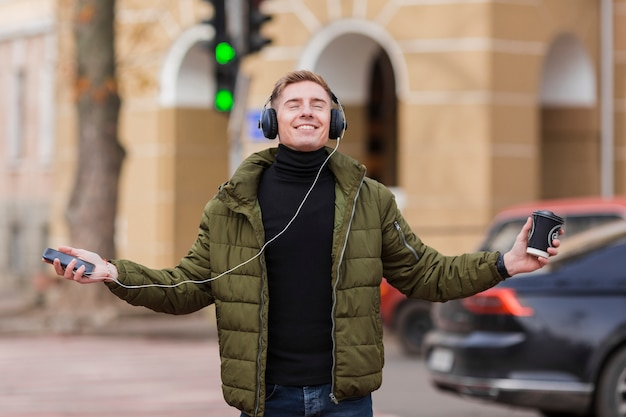 Junger mann des smiley, der musik auf kopfhörern auf den straßen hört