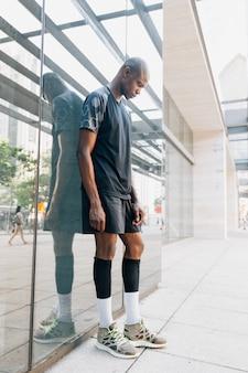 Junger mann des sportlichen jungen athleten, der gegen spiegel steht