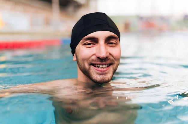 Junger mann des vorderansichtsmiley am swimmingpool