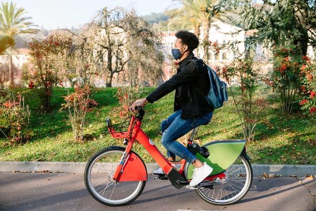 Junger mann, ein marokkanischer student, der ein gemeinsames elektrofahrrad in einem schönen park mit vielen bäumen bei sonnenuntergang fährt und eine gesichtsmaske für die coronavirus-pandemie von 2020 trägt