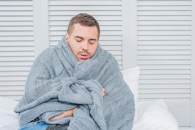 Junger mann eingewickelt in einen warmen schal, der von der kälte zittert