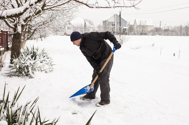Junger mann entfernt schnee in der nähe des vorstadthauses
