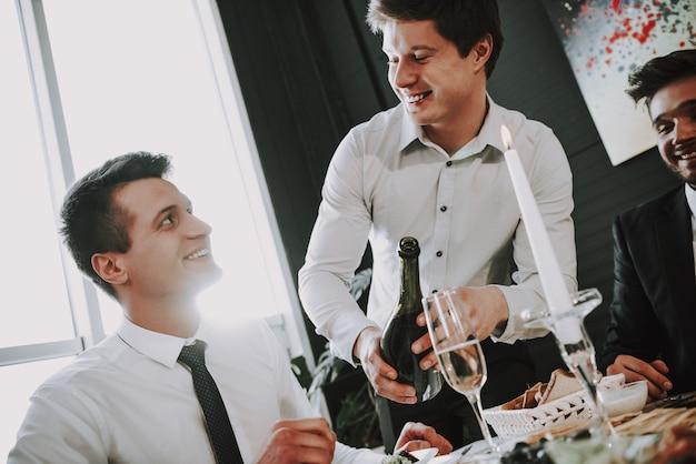 Junger mann entkorkt champagner. esstisch.
