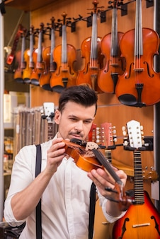 Junger mann erwägt violine in einem musikgeschäft.
